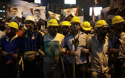 Supporters of Egypt's ousted President Mohammed Morsi hold sticks and wear protective gear during a march in Nasr City, where demonstrators have installed a camp and hold daily rallies, in Cairo, Egypt, late Tuesday, July 30, 2013 (photo credit: AP Photo/Hassan Ammar)