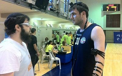 Joseph Gorowitz (left) helps a Russian player don tefillin after a basketball match (photo credit: Raphael Gellar/Times of Israel)