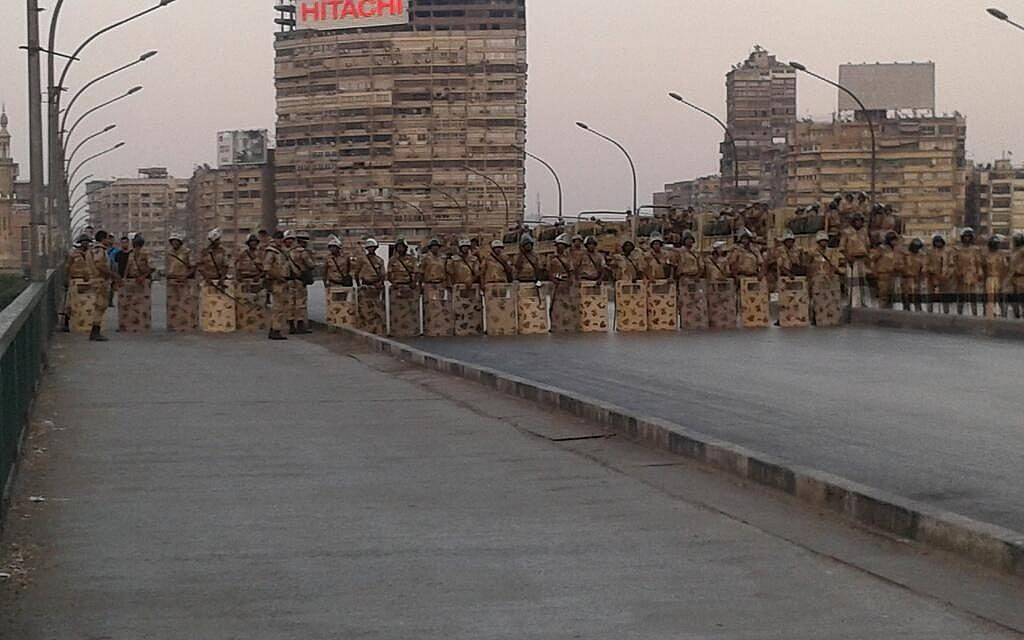 Troops in riot gear on a bridge across the Nile near Cairo University. (photo credit: Alastair Beach via Twitter)