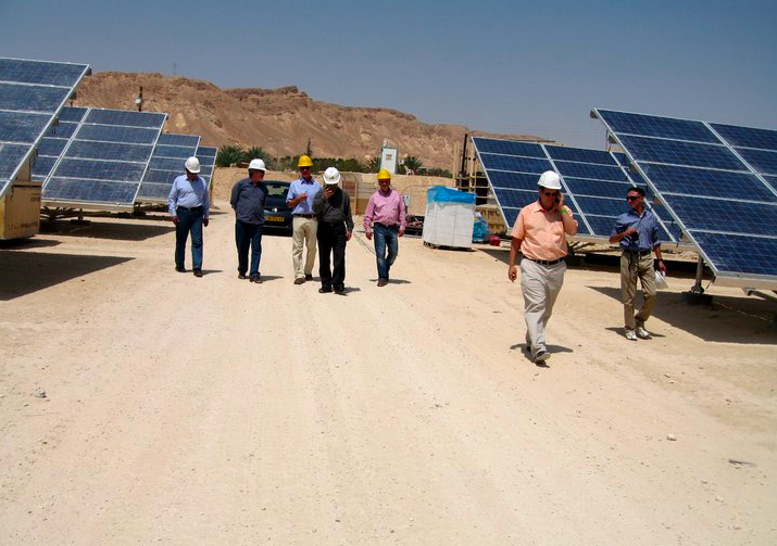 Yossi Abramowitz (in peach shirt) and his partners at the country's first solar field (Courtesy Yosef Abramowitz)