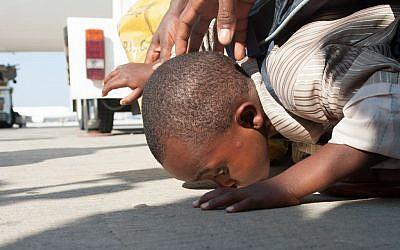 A child kisses the ground after arriving in Israel on Wednesday. (photo credit: Moshik Brin/Courtesy Jewish Agency)