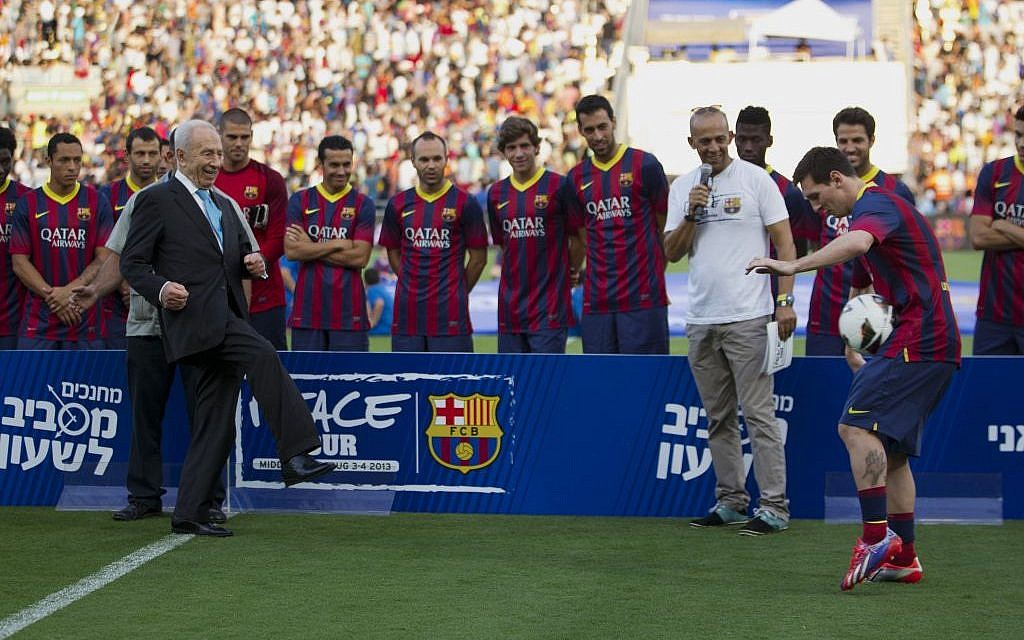 President Shimon Peres kicks the ball to FC Barcelona's Argentinian striker Lionel Messi during a football clinic session in Broomfield stadium in Tel Aviv, Israel, Sunday, Aug. 4, 2013. (photo credit: AP Photo/Ariel Schalit)