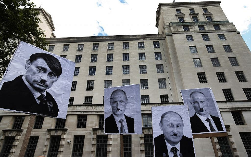 Protest signs displayed in London over the weekend liken Russian leader Vladimir Putin to Adolf Hitler. (AP Photo/Lefteris Pitarakis)