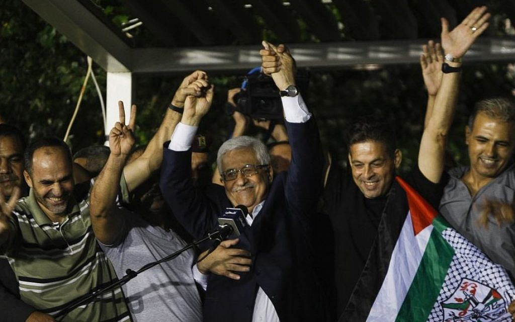 Palestinian Authority President Mahmoud Abbas, center, waves with the released Palestinian prisoners at his headquarters in the West Bank city of Ramallah on August 14 , 2013. (AP Photo/Majdi Mohammed)