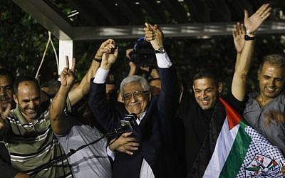 Palestinian Authority President Mahmoud Abbas, center, waves with the released Palestinian prisoners at his headquarters in the West Bank city of Ramallah on Wednesday, Aug. 14 , 2013. (photo credit: AP Photo/Majdi Mohammed)