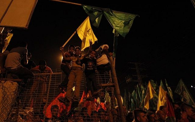 Palestinians celebrate and wave green Hamas and yellow Fatah flags as they wait for the released prisoners at a checkpoint at the entrance of Beit Hanoun between the northern Gaza Strip and Israel on Tuesday, Aug. 13, 2013. (photo credit: AP photo/Hatem Moussa)