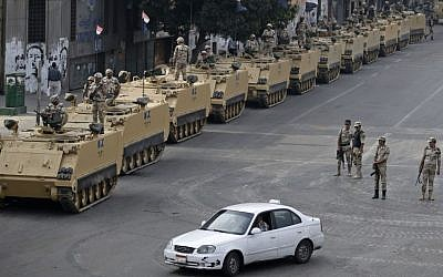 Egyptian army soldiers take their positions on top and next to their armored vehicles while guarding an entrance to Tahrir square, in Cairo on Friday, August 16, 2013. (photo credit: AP/Hassan Ammar)