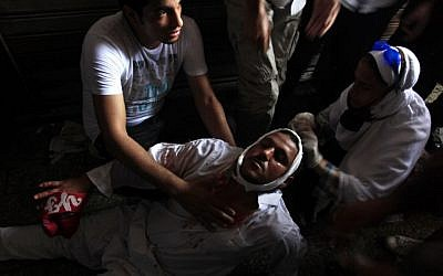 A wounded Egyptian man receives treatment on the ground during clashes between security forces and supporters of Egypt's ousted president Mohammed Morsi in Ramses Square, near the Al-Fath mosque, in downtown Cairo, Egypt, on Friday. (photo credit: AP Photo/Khalil Hamra)
