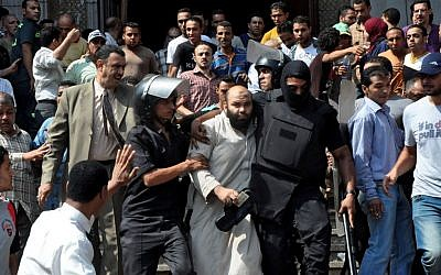 Egyptians security forces escort an Islamist supporter of the Muslim Brotherhood out of the al-Fatah mosque, after hundreds of Islamist protesters barricaded themselves inside the mosque overnight, following a day of fierce street battles that left scores of people dead, near Ramses Square in downtown Cairo, Egypt, Saturday, Aug. 17 (photo credit: AP/Hussein Tallal)