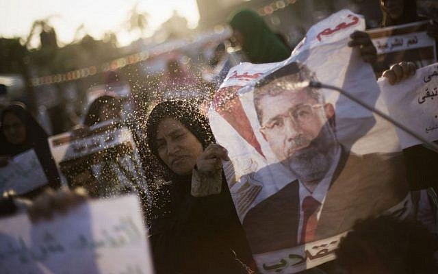 A supporter of Egypt's ousted President Mohammed Morsi sprays water on an Egyptian woman during a protest near Cairo University in Giza, Egypt, Thursday, August, 1, 2013. (Photo credit: AP/Manu Brabo)