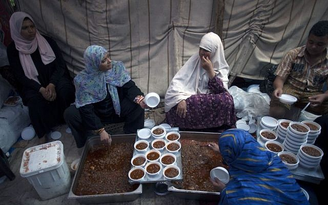 Supporters of Egypt's ousted president Mohammed Morsi serve food on plastic dishes to distribute to protesters outside Rabaah al-Adawiya mosque, where they have installed a camp and held daily rallies at Nasr City, Cairo, Egypt, Tuesday, Aug. 13, 2013. (photo credit: AP Photo/Khalil Hamra)