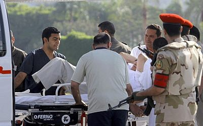 Egyptian medics and military policemen escort former Egyptian president Hosni Mubarak, 85, into an ambulance after he was flown by helicopter to the Maadi Military Hospital in Cairo, Egypt, on Thursday, August 22, 2013. (photo credit: AP/Amr Nabil)