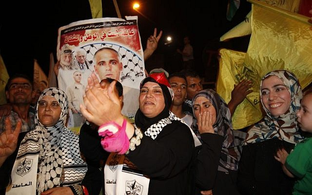 Relatives of Atef Sha'ath, one of the freed Palestinian prisoners, celebrate while waiting for his release at the checkpoint at the entrance of Beit Hanoun in Gaza, Tuesday, Aug. 13, 2013. (photo credit: AP Photo/Adel Hana)