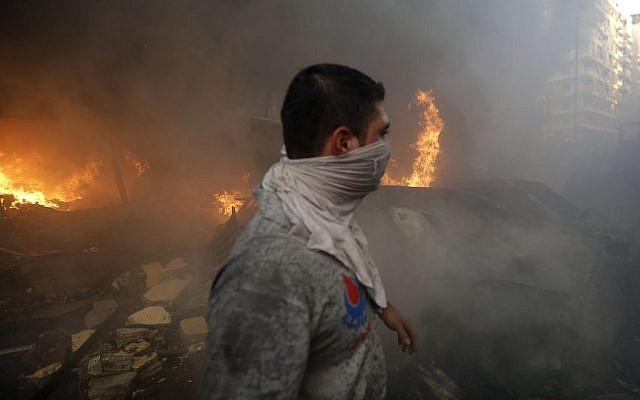 A Hezbollah civil defense worker walks past a burned car at the site of a bombing in a southern suburb of Beirut, Lebanon, Thursday, August 15, 2013 (photo credit: AP/Hussein Malla)
