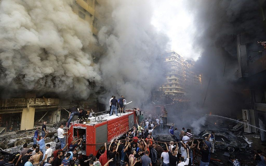 Lebanese citizens and Hezbollah supporters gather at the scene of a car bomb explosion in southern Beirut, Lebanon, Thursday Aug. 15, 2013. (Photo credit: AP/Hussein Malla)