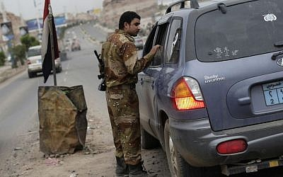 A Yemeni soldier inspects a car at a checkpoint on a street leading to the US embassy in Sanaa, Yemen, Sunday, Aug. 4, 2013. (Photo credit: AP/Hani Mohammed)