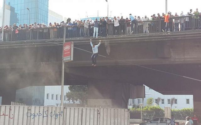 A man jumps off a bridge in Cairo to flee gunfire on Friday (photo credit: SarahCarr via Twitter)