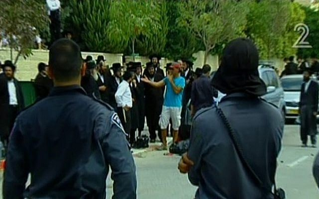 Police officers face off with ultra-Orthodox protesters in Beit Shemesh on Monday, Aug 12 (image capture: Channel 2)