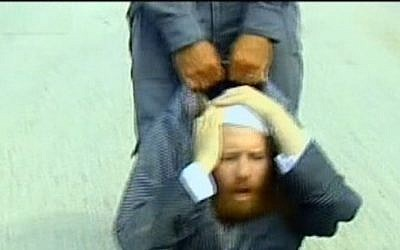 An ultra-Orthodox protester is dragged by a police officer at a construction site said to contain ancient Jewish graves, August 12, 2013 (photo credit: screen cap Channel 2 News)