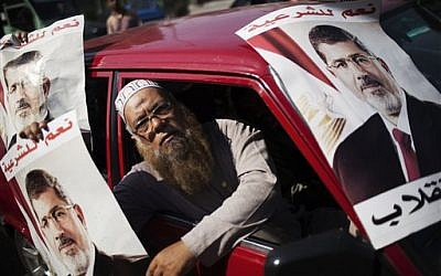 A supporter of Egypt's ousted President Mohammed Morsi holds a banner with Morsi's image, during a march against Egyptian Defense Minister Gen. Abdel-Fattah el-Sissi in the Nasr City section of Cairo, Friday, Aug. 2, 2013 (photo credit: AP Photo/Manu Brabo)