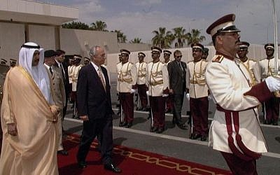 Shimon Peres and a Qatari official review an honor guard during a reception ceremony at the Doha airport, April 2, 1996 (photo credit: Avi Ohayon/GPO)