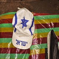 "A white hate adorned with the Jewish star of David and the word ""Israel"" hangs high on Damaka's wall (photo credit: Michal Shmulovich/ToI)"