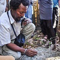 Danny Adeno Abebe, one of the organizers of the Samai trip for Ethiopian-Israeli teens, brushes grass from a Jewish cemetery outside Gondar, Ethiopia (photo credit: Michal Shmulovich/ToI)