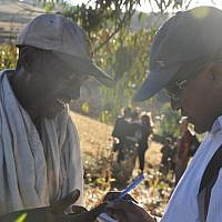 David Mihret, a prominent Ethiopian-Israeli community leader, asks a local Ethiopian farmer if he knows anything about the Jewish community that used to live in the area (photo credit: Michal Shmulovich/ToI)