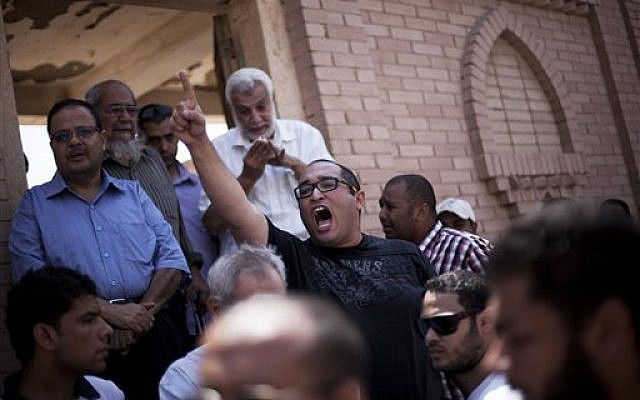 "A friend of Ammar Badie, 38, killed Friday by Egyptian security forces during clashes in Ramses Square, and also son of Muslim Brotherhood's spiritual leader Mohammed Badie, shouts, ""Allah is the greatest,"" while attending his burial in Cairo's Katameya district, Egypt, Sunday, Aug. 18, 2013 (photo credit: AP/Manu Brabo)"