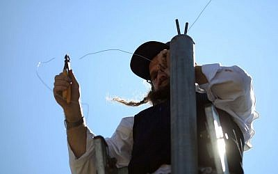 Illustrative photo of an ultra-Orthodox man hanging an eruv wire in the Gilo neighborhood of Jerusalem, Israel. (photo credit: Nati Shohat/Flash90/File)