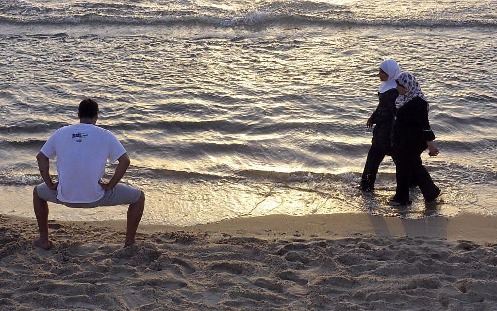 Palestininian women walk by an Israeli man on the beach in Tel Aviv. (photo credit: Serge Attal/Flash90)
