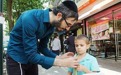 A Brooklyn Jewish man shows a lulav to a boy during Sukkot. (photo credit: Mendy Hechtman/FLASH90)