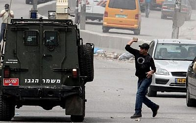Illustration. Palestinian protesters throw stones at an Israeli military car during a rally at the Qalandiya checkpoint, north of Jerusalem, on March 30, 2013. (photo credit: Issam Rimawi/Flash90)