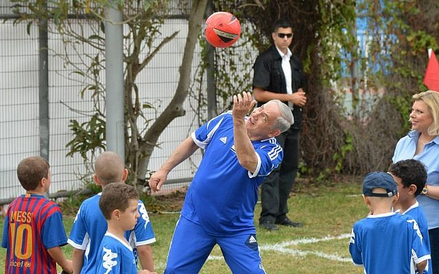 Prime Minister Benjamin Netanyahu plays with a soccer ball as he meets young cancer patients and the FC Barcelona soccer team, prior to FC Barcelona's open practice in Jaffa's Bloomfield Stadium, near Tel Aviv, Sunday, August 4, 2013 (photo credit: Avi Ohayon/GPO/Flash90)