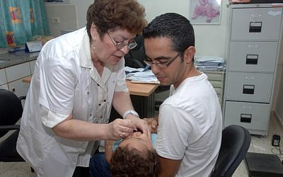 Take two drops and call me in the morning. An Israeli child receives the oral vaccination against polio in Beersheba in August 2013. (photo credit: Dudu Greenspan/FLASH90)