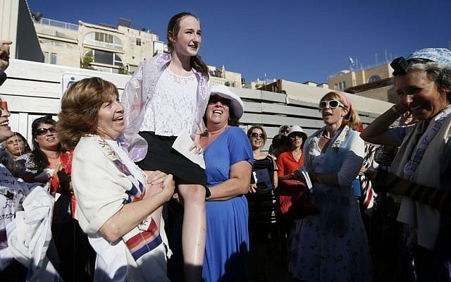 Hoffman, left, holds up a young girl during her bat mitzva at Western Wall on August 7, 2013. (photo credit: Miriam Alster/Flash90)