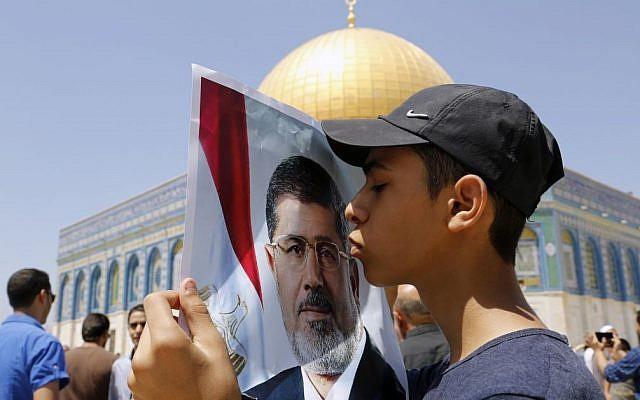 A Palestinian child kisses a poster bearing the image of ousted Egyptian president Mohammed Morsi at a protest on the Temple Mount in Jerusalem, on Friday (photo credit: Sliman Khader/Flash90)