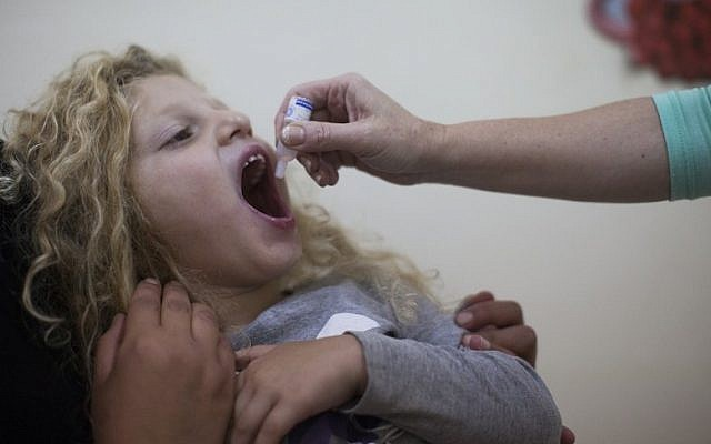 A child is inoculated with the oral polio vaccine at a children's health clinic in Jerusalem (Yonatan Sindel/Flash90)
