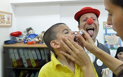 A medical clown makes faces as an Israeli boy receives polio vaccination, August 19, 2013. (photo credit: Yossi Zeliger/Flash90)
