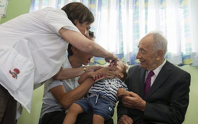 President Shimon Peres, right, watches on as a medical worker administers a dose of polio vaccine to a young boy at a clinic in Jerusalem, on Wednesday (photo credit: Flash90)