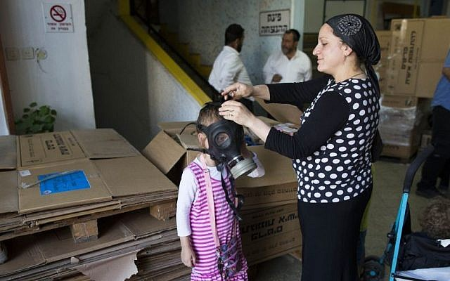 An Israeli woman shows her daughter how to put on a gas mask at a distribution center in Jerusalem, Tuesday, August 27, 2013 (photo credit: Yonatan Sindel/Flash90)