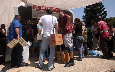 Israelis carry boxes with gas masks at a distribution center in Tel Aviv on August 28, 2013.(photo credit: Roni Schutzer/Flash90)