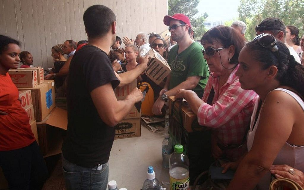 Israelis carry boxes with gas masks at a distribution center in Tel Aviv on August 28, 2013. (Photo credit: Roni Schutzer/Flash90)