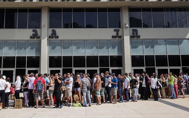Israelis carry gas mask boxes outside a  distribution center in the northern Israeli city of Haifa, on August 29, 2013. (photo credit: Avishag Shaar Yashuv/Flash90)