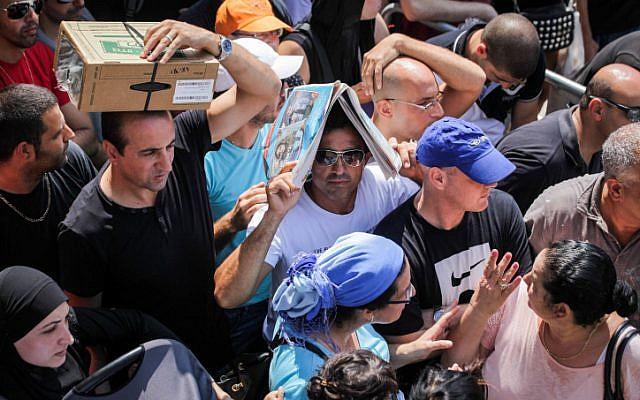 Israelis at a gas mask distribution center in Haifa on Thursday (photo credit: Avishag Shaar Yashuv/Flash 90)