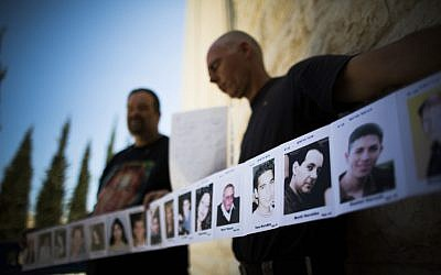 Relatives of Israelis killed in terror attacks holding signs as they demonstrate outside the Supreme Court in Jerusalem on August 11, 2013. (Photo credit: Yonatan Sindel/Flash90)