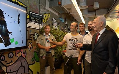 President Shimon Peres has some fun with one of the games being developed at Google's Campus TLV (photo credit: Marc Neiman/GPO)