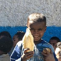 A young boy shows the bread and snacks he gets at the Jewish Agency-run synagogue in Gondar (photo credit: Michal Shmulovich/ToI)