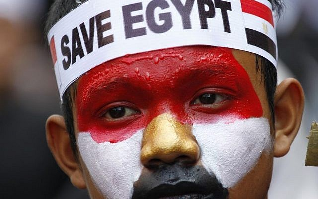 In Jakarta, Indonesia on Friday, an Indonesian Muslim man with his face painted in the colors of the Egyptian flag takes part in a rally calling for an end to the violence used against Egypt's supporters of ousted president Mohammed Morsi in Egypt. (photo credit: AAP Photo/Achmad Ibrahim)