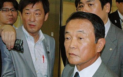 Japanese Finance Minister Taro Aso is surrounded by reporters at the ministry in Tokyo Thursday, August 1, 2013. (photo credit: AP/Kyodo News)
